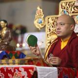 Karmapa with damaru on throne