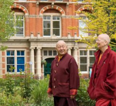 Lama Yeshe and Lama Zangmo walking in park with building in background